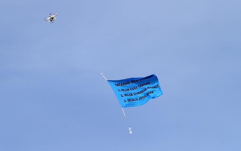 Sebuah bendera bertuliskan protokol kesehatan tatanan normal baru diterbangkan drone atau pesawat tanpa awak di kawasan Bundaran Digulis Pontianak, Kalimantan Barat, Sabtu (27/6/2020). Aksi yang dilakukan Lanud Supadio bersama Enggang Drone Community dan Federasi Aero Sport Indonesia tersebut bertujuan untuk mengedukasi masyarakat juga membantu pemerintah dalam mencegah penyebaran Covid-19. ANTARA FOTO - Jessica Helena Wuysang