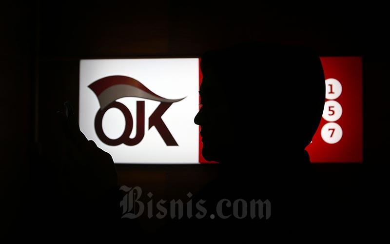 Ilustrasi-Karyawan berada di dekat logo Otoritas Jasa Keuangan di Jakarta, Jumat (17/1/2020). - Bisnis/Abdullah Azzam