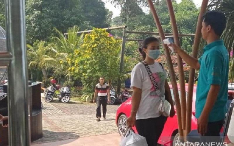 Petugas di pintu masuk wisata air The Jhons di Desa Babakankaret, Kecamatan Cianjur, Jawa Barat, kembali beroperasi dengan menerapkan protokol kesehatan sesuai yang diterapkan pemerintah. - Antara