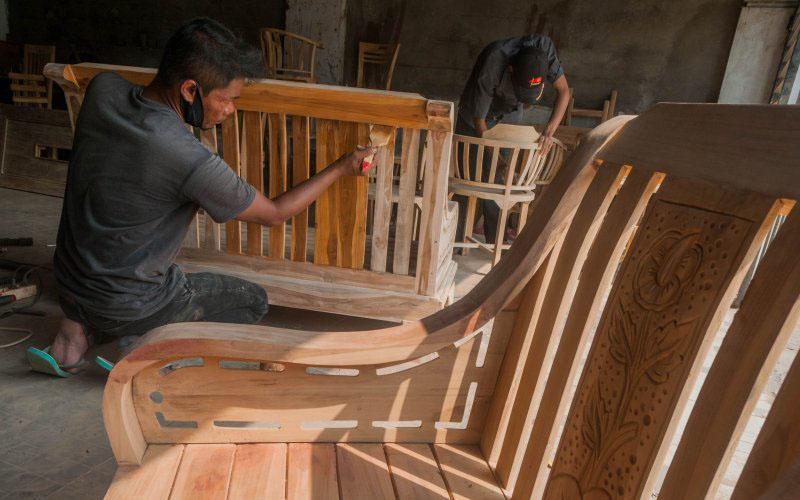 Pekerja menyelesaikan tahap produksi mebel kayu jati di Desa Mekar Agung Lebak, Banten. Kerajinan mebel berupa kursi, meja, dan tempat tidur yang berbahan dasar limbah kayu jati dan mahoni dengan harga berkisar Rp13 juta hingga Rp5 juta per unit. - Antara/Mansyur S