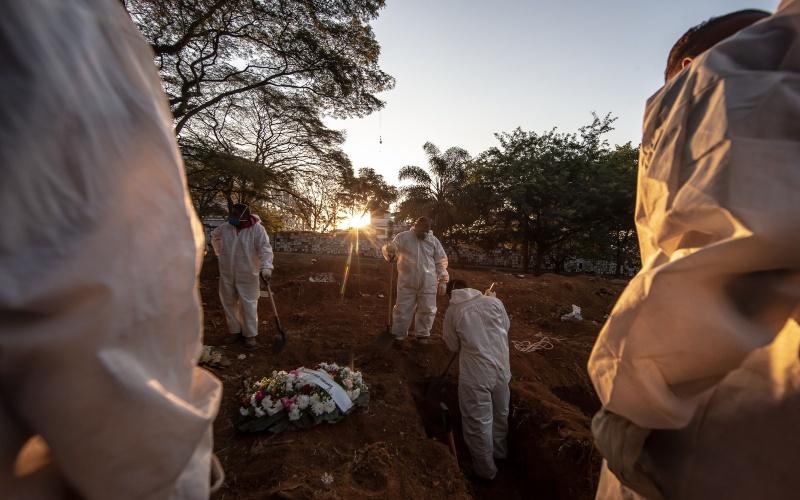Petugas memakamkan korban virus corona di Brasil. - Bloomberg