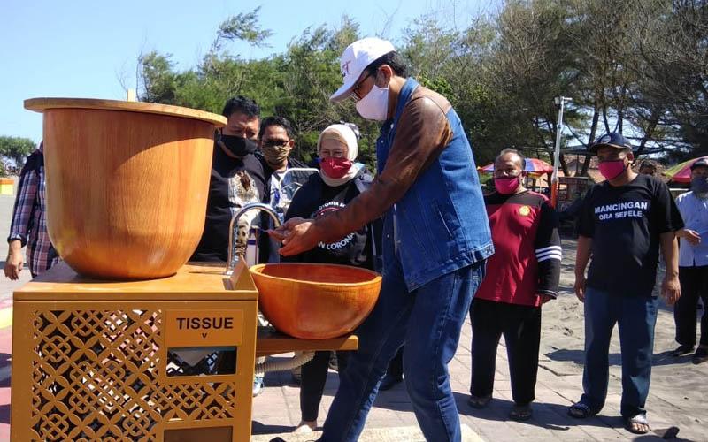 Kepala Dinas Pariwisata DIY, Singgih Raharjo mencoba tempat cuci tangan yang disediakan di kawasan Pantai Parangtritis, Sabtu (13/6/2020).  - JIBI/Ujang Hasanudin
