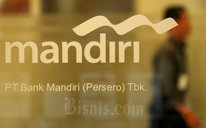 Karyawan melintas di dekat logo milik Bank Mandiri di Jakarta, Kamis (8/8/2019). Bisnis - Arief Hermawan P