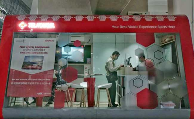 Karyawan melayani pelanggan di pusat layanan pelanggan Telkomsel di Bandara Soekarno Hatta, Tangerang, Senin(27/1/2020). Bisnis - Himawan L Nugraha