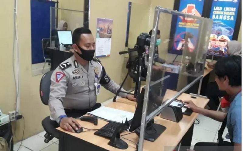 Anggota kepolisian sedang mengurus permohonan SIM oleh masyarakat. - Antara
