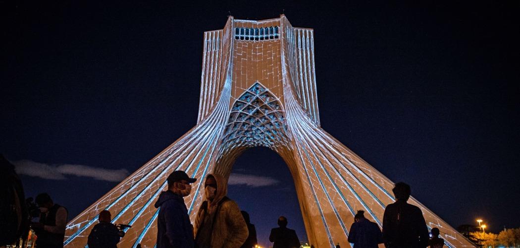 Warga menonton atraksi cahaya yang digelar untuk mendukung perlawanan terhadap Covid-19 di Menara Azadi, Teheran, Iran, Selasa (31/3/2020). - Bloomberg/Ali Mohammadi\\n