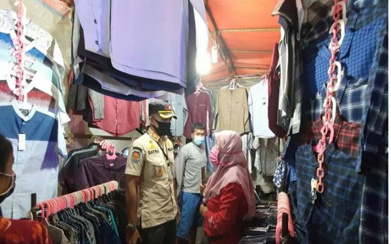 Kasie PPNS Satpol PP Jakarta Pusat Gatra Pratama Putra saat meminta pedagang Pasar Jiung Kemayoran untuk menutup lapaknya di tengah operasi PSBB yang memasuki tahap 3, Jumat (22/5/2020). - Antara