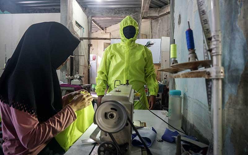 Penjahit menyelesaikan pembuatan baju alat pelindung diri (APD) berbahan parasut di Sekarpace, Solo, Jawa Tengah, Jumat (27/3/2020). Penjahit pengaku saat ini mengalami kesulitan bahan baku baju pelindung diri (APD) yang banyak dipesan tenaga medis dan Puskesmas. ANTARA FOTO - Mohammad Ayudha