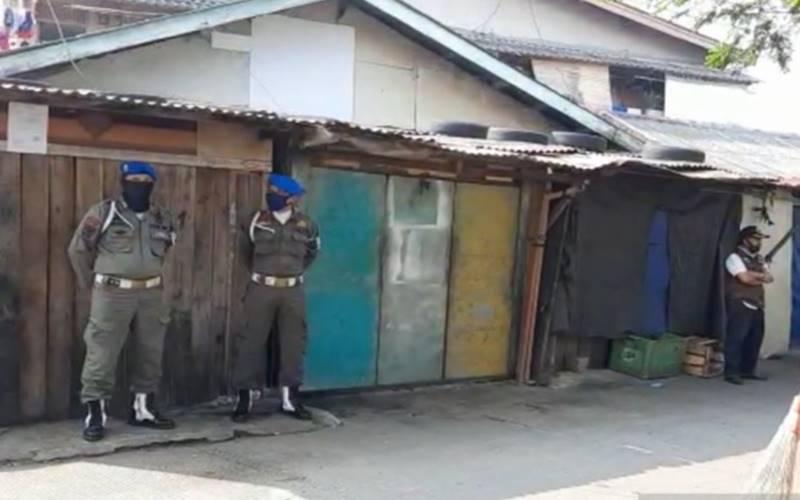 Toko pedagang yang tutup dijaga aparat Satuan Polisi Pamong Praja Kecamatan Kembangan untuk sterilisasi cegah penyebaran Covid-19 di Pasar Kemiri, Kembangan, Jakarta Barat, Selasa (1/7/2020). - Antara\n\n