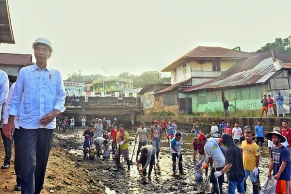 Presiden Joko Widodo (kiri) meninjau kegiatan pengerukan atau normalisasi Sungai Wai Hatukau di Desa Batu Merah, Ambon, Maluku, Rabu (14/2). - Setkab