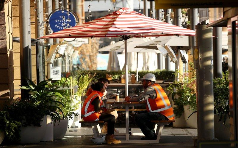 Petugas kontruksi tengah menikmati kopi di sebuah kafe, di Selandia Baru -  Bloomberg