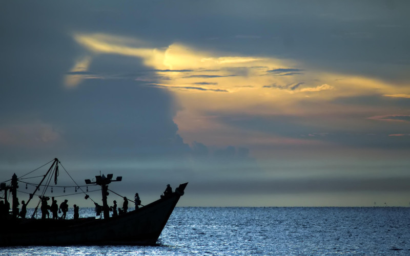 Kapal nelayan melintas dengan latar belakang matahari terbit di perairan Selat Malaka, Lhokseumawe, Aceh, Rabu (8/4 - 2020). /Antara