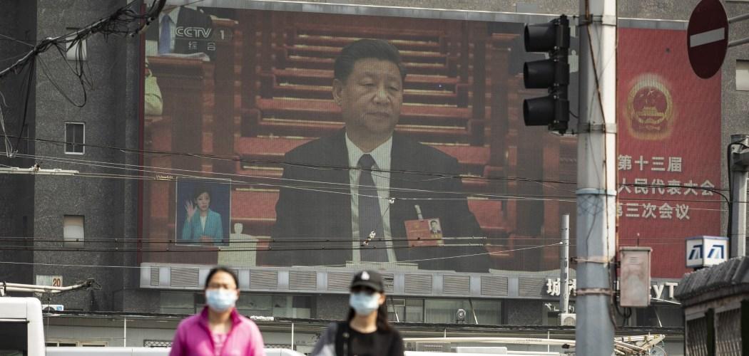 Warga berjalan di depan layar monitor yang menampilkan Presiden China Xi Jinping dalam National People's Congress di Beijing, China, Jumat (22/5/2020). - Bloomberg/Qilai Shen\\n