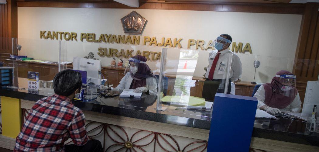 Petugas pajak dengan melayani wajib pajak dari balik sekat kaca guna mencegah Covid-19. - Antara / Mohammad Ayudha