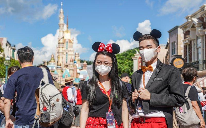 Pelancong berfoto mengunakan masker di Disneyland Hong Kong. -  Bloomberg