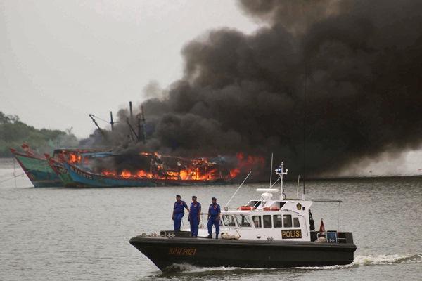 Anggota Polisi Air (Polair) meledakkan kapal nelayan asing di kawasan perairan Medan Belawan, Sumatra Utara, Sabtu (1/4). - ANTARA FOTO/Septianda Perdana