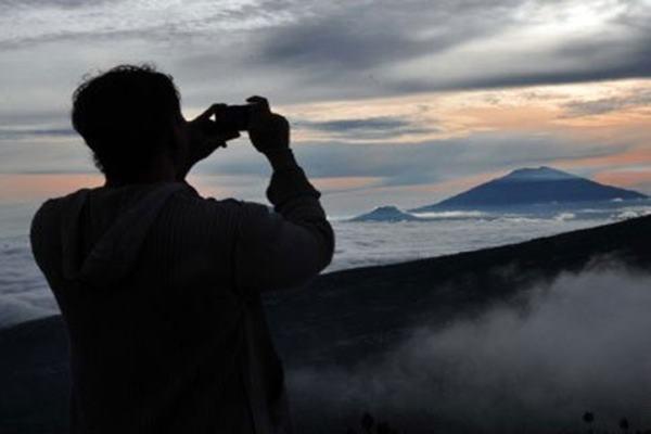 Seorang warga mengabadaikan pemandangan saat matahari terbit di lereng Gunung Sindoro di kawasan wisata alam Posong, Kledung, Temanggung, Jawa Tengah. - Antara