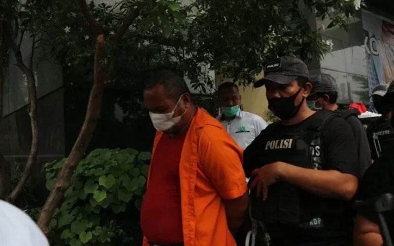 John Kei dikawal oleh petugas Polda Metro Jaya setelah dihadirkan dalam jumpa pers di Mako Polda Metro Jaya pada Senin (22/6/2020)./Antara - Fianda Rassat