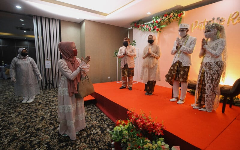 Tamu undangan memberikan ucapan selamat kepada pasangan pengantin Kumala dan Putri beserta keluarganya dengan menjaga jarak fisik saat simulasi resepsi pernikahan di masa normal baru di Hotel Royal Singosari Cendana, Surabaya, Jawa Timur, Senin (6/7/2020). Kegiatan simulasi resepsi pernikahan tersebut bertujuan untuk mengedukasi masyarakat tentang pentingnya penerapan protokol kesehatan dalam acara pernikahan guna mencegah penyebaran dan penularan Covid-19 di masa normal baru. - Antara/Moch Asim
