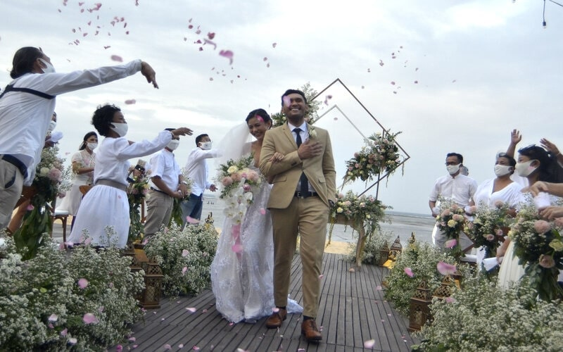 Sejumlah tamu undangan menyambut pasangan pengantin saat simulasi penyelenggaraan kegiatan pernikahan di kawasan Nusa Dua, Badung, Bali, Senin (6/7/2020). Kegiatan simulasi yang diselenggarakan Bali Wedding Association tersebut dilakukan sebagai upaya sosialisasi dan pedoman penyelenggaraan kegiatan pernikahan yang menerapkan protokol kesehatan pencegahan Covid-19 secara ketat selama masa normal baru. - Antara/Fikri Yusuf