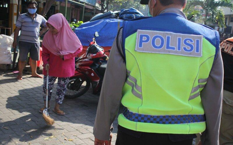 Petugas menghukum warga yang tidak memakai masker untuk menyapu jalan saat razia di Pasar Setro, Surabaya, Jawa Timur, Rabu (8/7/2020). Tindakan itu guna mendisiplinkan warga untuk patuh terhadap protokol kesehatan pencegahan penularan Covid-19. - Antara/Didik Suhartono
