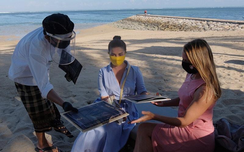 Pekerja menggunakan alat pelindung diri saat melayani wisatawan di Hotel Puri Santrian, Sanur, Denpasar, Bali, Kamis (2/7/2020). - Antara/Nyoman Hendra Wibowo\n