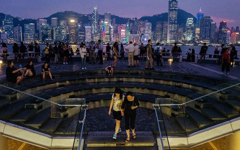 Warga Hong Kong menikmati malam di tepi laut di distrik Tsim Sha Tsui sambi menyaksikan bangunan di seberang Pelabuhan Victoria terang benderang,/Bloomberg - Anthony Kwan