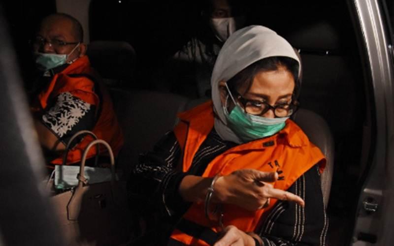 Bupati Kutai Timur Ismunandar (kiri) bersama istri yang merupakan Ketua DPRD Kutai Timur Encek Unguria (kanan) dibawa menuju mobil tahanan usai ditetapkan sebagai tersangka pascaterjaring Operasi Tangkap Tangan (OTT) di Gedung KPK, Jakarta, Sabtu (4/7/2020). - ANTARA/Indrianto Eko Suwarso\n\n
