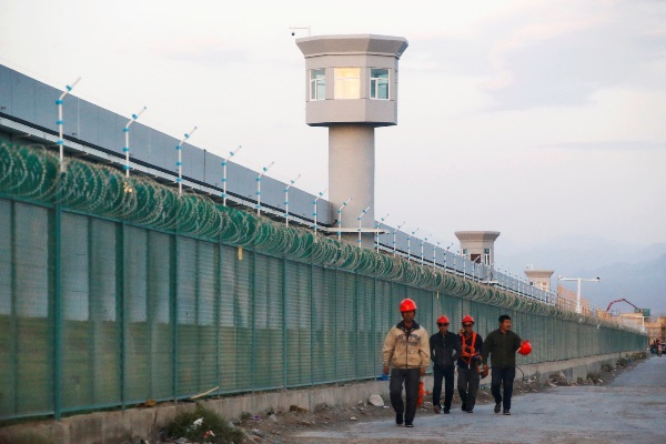 Beberapa pekerja berjalan di luar pagar lokasi yang secara resmi disebut sebagai pusat edukasi vokasional di Dabancheng, Xinjiang, Wilayah Otonomi Uighur, China, Selasa (4/9/2018). - Reuters/Thomas Peter