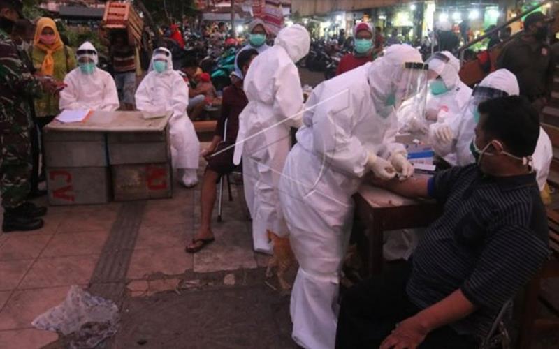 Petugas dari Dinkes Surabaya melakukan pemeriksaan cepat COVID-19 terhadap warga di Pasar Keputran, Surabaya, Jawa Timur, Selasa (12/5/2020). - Antara