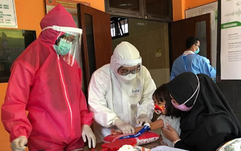 Ilustrasi-Petugas kesehatan melakukan pemeriksaan menggunakan alat tes diagnostik cepat untuk mendeteksi penularan Covid-19 pada seorang anak. - Antara/Eka AR