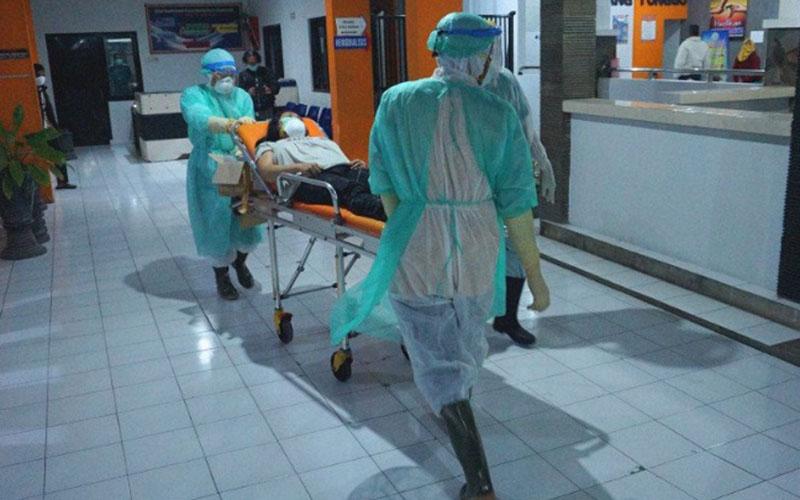 Petugas medis mengenakan alat pelindung diri mendorong ranjang beroda tempat pasien berstatus dalam pengawasan corona menuju ruang isolasi RSUD dr. Iskak di Tulungagung, Jawa Timur, pada Jumat (13/3/2020). - Antara
