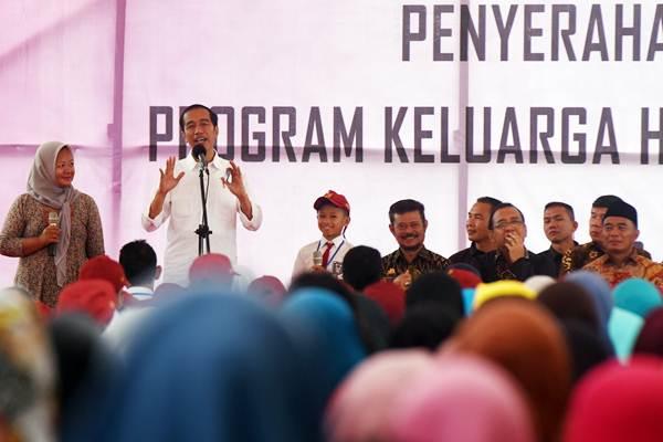 Presiden Joko Widodo (kedua kiri) berdialog dengan warga saat penyerahan secara simbolik Kartu Program Keluarga Harapan (PKH) dan Kartu Indonesia Pintar (KIP) di Lapangan Syech Yusuf, Kabupaten Gowa, Sulawesi Selatan, Kamis (15/2/2018). - ANTARA/Yusran Uccang