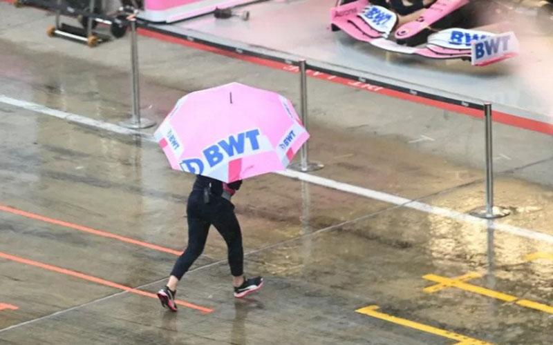 Anggota tim Racing Point menggunakan payung melintasi jalur pit sirkuit Red Bull Ring, Austria, yang diguyur hujan sebelum sesi latihan bebas F1 GP Styria pada Sabtu (11/7/2020)./Antara - Reuters