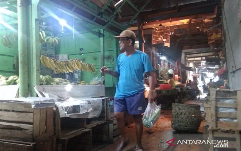 Pegunjung sedang menenteng kantong plastik berisi belanjaannya di Pasar Cempaka Putih, Jakarta Pusat, Jumat (28/2/2020). - ANTARA/Mochamad Firdaus