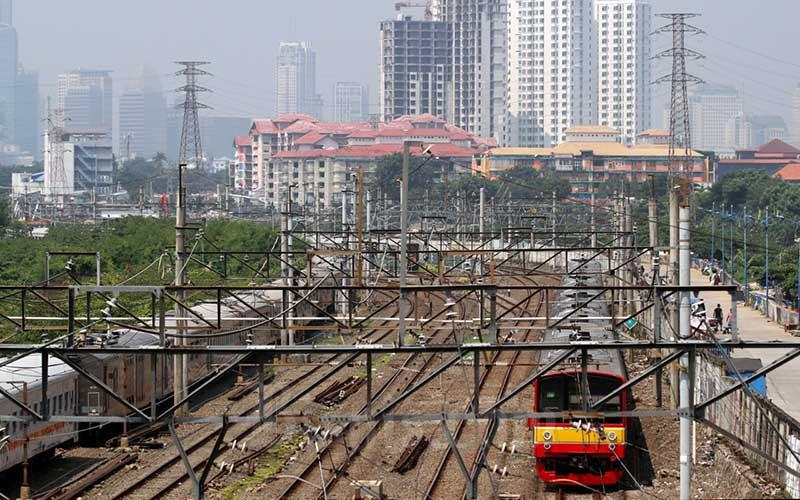 Rangkaian kereta rel listrik (KRL) melintas di kawasan Tanah Abang, Jakarta, Minggu (19/4/2020). Bisnis - Arief Hermawan P