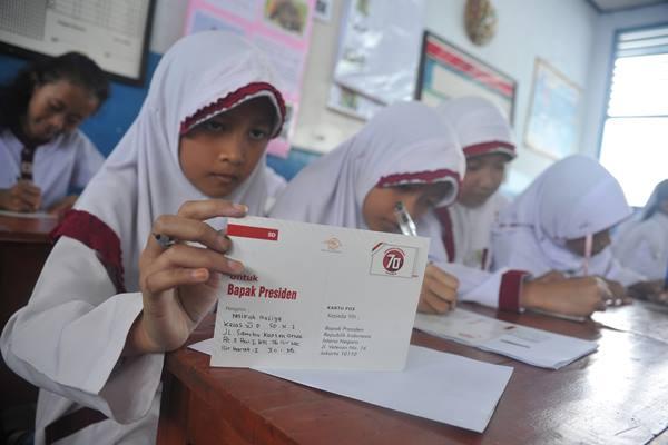 Siswi Sekolah Dasar membaca ulang surat yang akan mereka kirimkan kepada Presiden Joko Widodo di ruang kelas Sekolah Dasar Negeri 1 Palembang, Kamis (20/8). - Antara