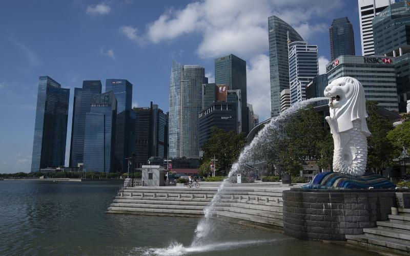 Patung Merlion berdiri di depan gedung-gedung pencakar langit di Singapura, Selasa (24/3/2020). - Bloomberg/Wei Leng Tay