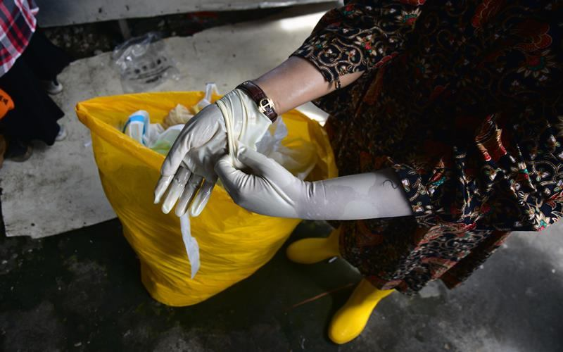 Seorang tenaga kesehatan melepaskan sarung tangan medis usai mengambil sampel untuk tes usap (swab) COVID-19 massal di Pasar Sukaramai, Kota Pekanbaru, Riau, Jumat (26/6/2020). Kementerian Lingkungan Hidup dan Kehutanan mencatat total limbah medis infeksius di Indonesia hingga 8 Juni 2020 mencapai lebih dari 1.100 ton yang harus dimusnahkan secara khusus karena tergolong limbah B3 dan berpotensi jadi sumber penularan Virus Corona baru ANTARA FOTO - FB Anggoro