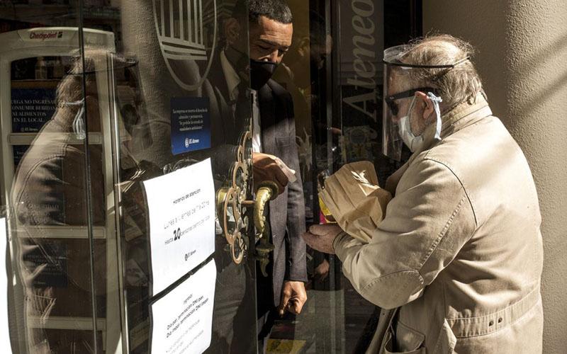 Seorang pengunjung toko mengenakan masker dan pelindung wajah saat berbelanja di sebuah toko di Buenos Aires, Argentina, pada 14 Mei 2020./Bloomberg - Sarah Pabst
