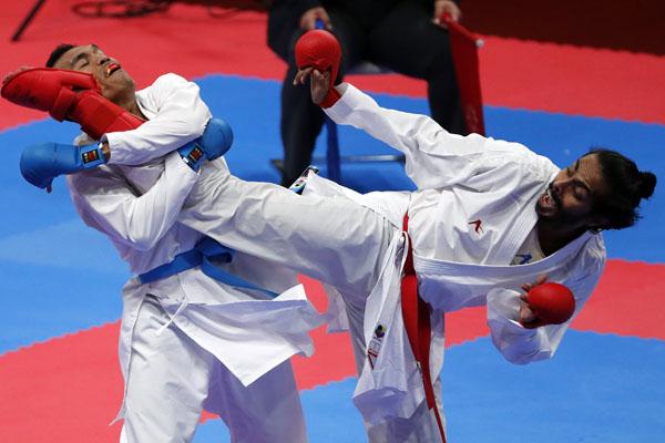 Karateka Indonesia Jintar Simanjuntak (kiri) saat berlaga melawan karateka Uni Emirat Arab,Ahmed Al-Hadhrami, untuk perebutan medali perunggu Minggu 26 Agustus 2018. - Reuters/IsseiKato