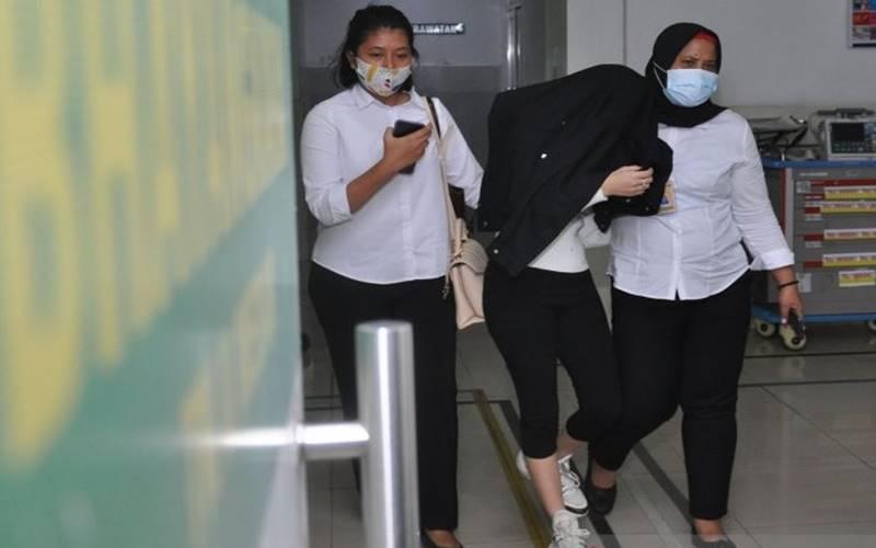 Personel kepolisian membawa artis berinisial H (tengah) saat menjalani pemeriksaan kesehatan di Rumah Sakit Bhayangkara Polda Sumut, Medan, Sumatra Utara, Senin (13/7/2020). H yang merupakan selebgram dan artis Film Televisi (FTV) tersebut ditangkap Polrestabes Medan dari sebuah hotel yang diduga terlibat dalam kasus prostitusi. - ANTARA/Septianda Perdana