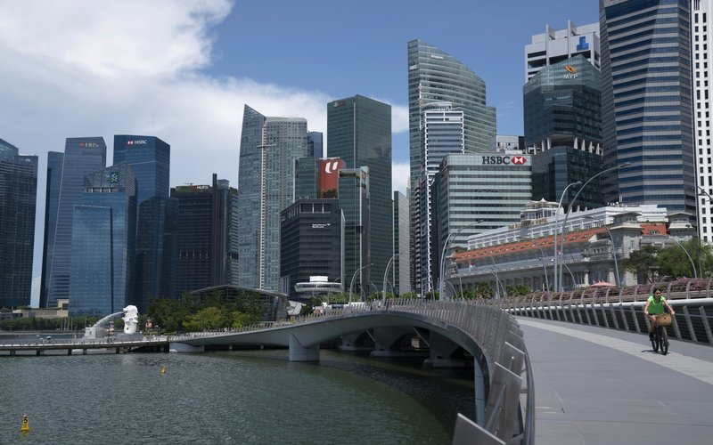 Warga Singapura bersepeda di dekat patung Marlion -  Bloomberg