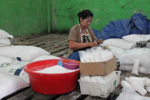 Salah satu pedagang gula dipasar tradisional sedang mengemasi gula pasir untuk dijual kembali  -  Arief Rahman