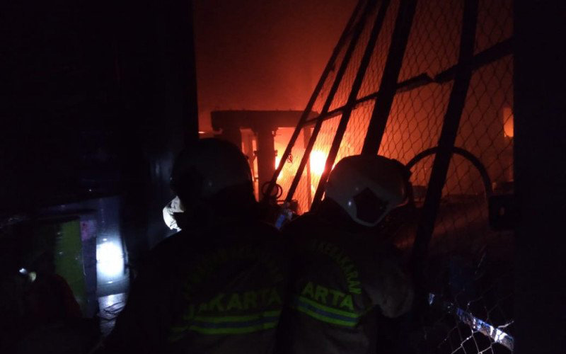 Petugas pemadam kebakaran menjinakkan api pada kebakaran pabrik cat di Jalan Kamal Raya 8 RT04/020 Tegal Alur, Kalideres Jakarta Barat, Kamis malam 16 Juli 2020). - Antara/dokumentasi Damkar Jakarta Barat