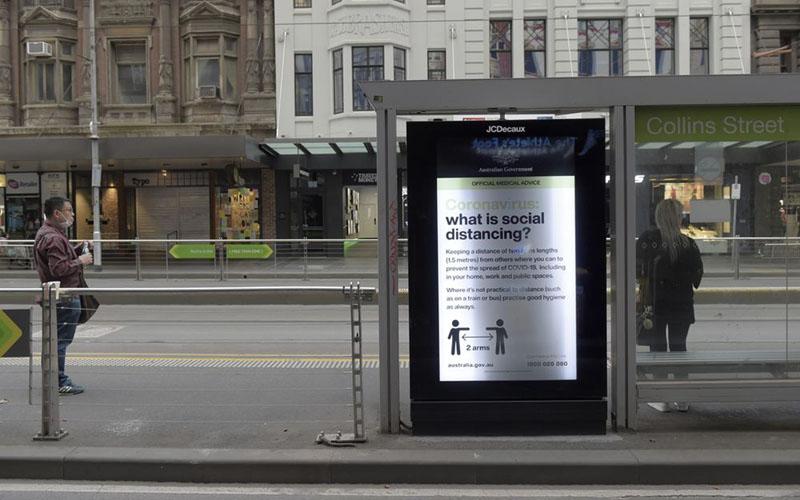 Tanda layanan publik mengenai jarak sosial ditampilkan di halte trem saat lockdown akibat pandemi corona di Melbourne, ibu kota Negara Bagian Victoria, Autstralia pada 23 Maret 2020./Blomberg - Carla Gottgens