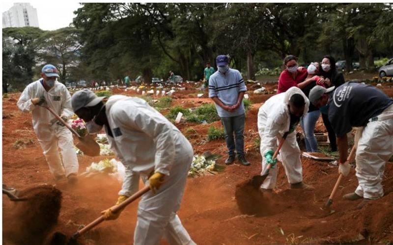 Kerabat menyaksikan para penggali berpakaian pelindung mengubur peti jenazah seorang pria, yang meninggal dunia akibat Covid-19 di pemakaman Vila Formosa, pemakaman terbesar di Brasil, di Sao Paulo, Brasil, Rabu (13/5/2020). - Antara