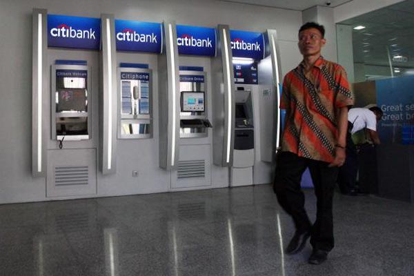 Pejalan kaki berjalan melewati deretan mesin anjungan tunai mandiri Citibank di Jakarta, belum lama ini - Bisnis/Dedi Gunawan