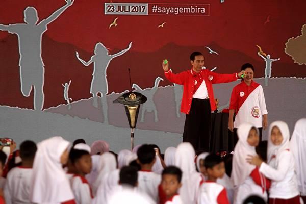 Presiden Joko Widodo beserta Ibu Negara Iriana Jokowi menghibur anak-anak dengan bermain sulap pada acara puncak perayaan Hari Anak Nasional 2017 di Pekanbaru, Riau, Minggu (23/7). ANTARA FOTO - Rony Muharrman