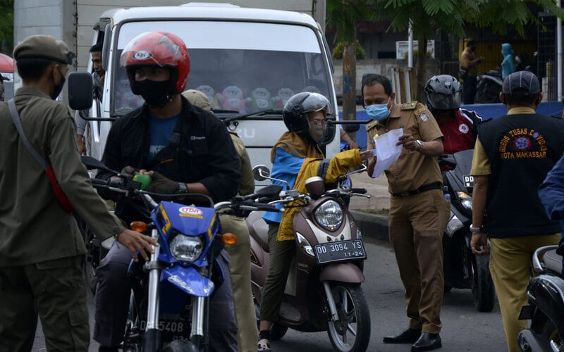 Petugas gabungan memeriksa surat keterangan bebas Covid-19 kepada sejumlah pengendara di perbatasan Makassar dan Kabupaten Gowa, Sulawesi Selatan, Senin (13/7/2020). Pemerintah Kota Makassar memberlakukan pemeriksaan surat keterangan bebas Covid-19 kepada warga yang akan memasuki kota Makassar sebagai upaya menekan penyebaran Covid-19. - Antara/Abriawan Abhe